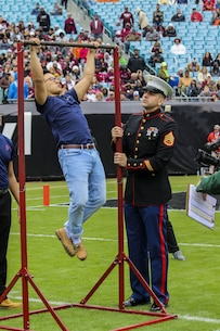 Staff Sergeant Bruno Bego, canvassing recruiter with Recruiting Substation Jacksonville, Recruiting Station Jacksonville, conducts a pull-up challenge during the TaxSlayer Bowl, Dec. 30, 2017, at EverBank Field in Jacksonville, Florida. Future Marines participated in a pull-up challenge to test their strength against other teams in front of the fans of Mississippi State University and the University of Louisville. (U.S. Marine Corps Photo by Sgt. Tony Simmons)