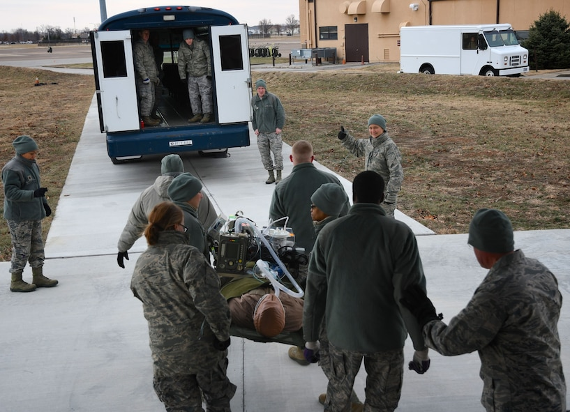 "At upper right, Master Sgt. Aubrie Miskell gives the ""thumbs up"" sign and motions the next group of 932nd Aeromedical Staging Squadron (ASTS) members to move up with their litter, and load a bus for patient movement. The 932nd Airlift Wing worked improving and refining skills at the unit during the very cold Unit Training Assembly Jan. 7, 2018, at Scott Air Force Base, Ill. The 932nd Medical Squadron, 932nd Aeromedical Evacuation Squadron and 932nd Aeromedical Staging Squadron Airmen learned together on first aid skills and C-130 load checks. Simulated patients were moved safely on to a waiting bus, and then out to the aeromedical crew at the C-130 simulator. The compact, highly-packed training was designed to lead people and execute any future medical missions.  (U.S. Air Force photo by Lt. Col. Stan Paregien)"