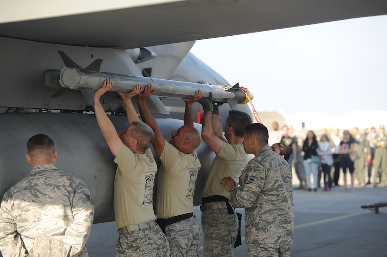 U.S. Air Force colonels load munitions onto an F-15 Eagle during the Chiefs versus Eagles Weapons Loading Competition Jan. 3, 2018, on Kadena Air Base, Japan. Each team had to load one AIM-9X heat seeking missile to the aircraft as quickly as possible. (U.S. Air Force photo by Staff Sgt. Micaiah Anthony)