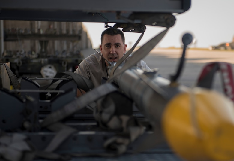 U.S. Air Force Chief Master Sgt. Davick Hansen, 18th Equipment Maintenance Squadron superintendent, inspects an AIM-9X heat seeking missile during the Chiefs versus Eagles Weapons Load competition Jan. 3, 2018, on Kadena Air Base, Japan. The competition pitted a team of chief master sergeants against a team of colonels to determine which group could prepare the aircraft for combat the fastest with the fewest procedural errors. (U.S. Air Force photo by Staff Sgt. Micaiah Anthony)