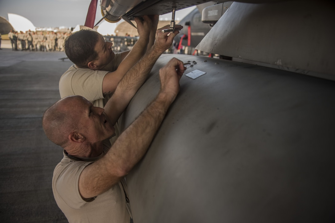U.S. Air Force Chief Master Sgt. Daniel Taylor, front, 18th Maintenance Group superintendent and Chief Master Sgt. Edward Fitzgerald, 18th Civil Engineer Group superintendent, load an AIM-9X heat seeking missile onto an F-15 Eagle during the Chiefs versus Eagles Weapons Load Competition Jan. 3, 2018, on Kadena Air Base, Japan. The competition was held before an annual weapons loading competition where the top teams from the 44th and 67th Aircraft Maintenance Units competed for the title of best weapons load team. (U.S. Air Force photo by Staff Sgt. Micaiah Anthony)