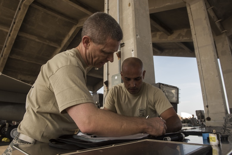 U.S. Air Force Col. Britt Hurst, left, 18th Operations Group commander, and Col. Tony Lombardo, 18th Maintenance Group commander, check forms during the Chiefs versus Eagles Weapons Loading competition Jan. 3, 2018, on Kadena Air Base, Japan. Each team had to load one AIM-9X heat seeking missile to the aircraft as quickly as possible. (U.S. Air Force photo by Staff Sgt. Micaiah Anthony)