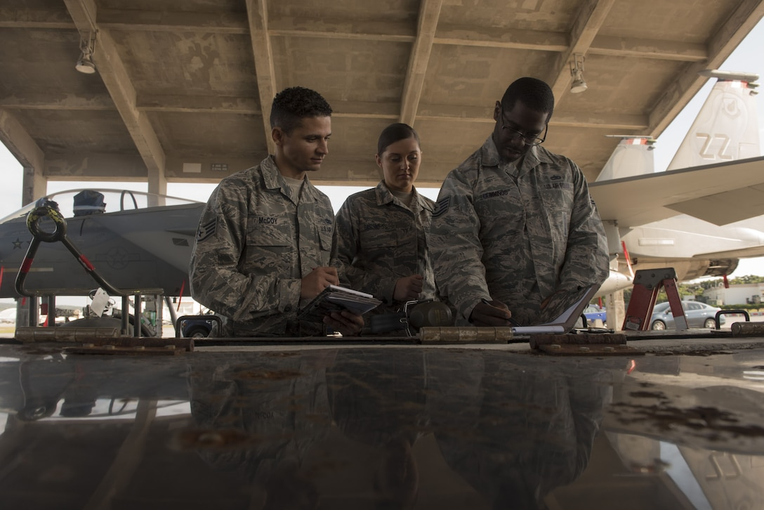 U.S. Air Force Staff Sgt. Michael McCoy, left, 18th Maintenance Group weapons load crew chief, Airman 1st Class Victoria Barsness, center, 18th MXG weapons load crew member, and Tech. Sgt. John Cummings, 18th MXG loading standardization crew member, calculate scores during the Chiefs versus Eagles Weapons Load Competition Jan. 3, 2018, on Kadena Air Base, Japan. The competition pitted a team of chief master sergeants against a team of colonels on who could prepare the aircraft for combat the fastest with the fewest procedural errors. (U.S. Air Force photo by Staff Sgt. Micaiah Anthony)