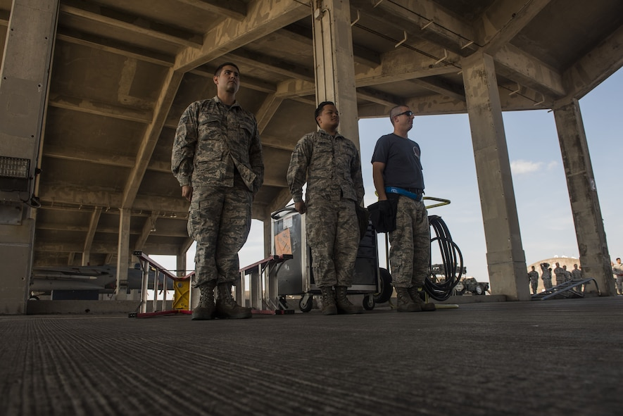 U.S. Air Force Airmen from the 44th Aircraft Maintenance Unit, stand at attention after loading munitions onto an F-15 Eagle during an annual weapons load competition Jan. 3, 2018, on Kadena Air Base, Japan. Airmen from the 44th AMU won the competition against Airmen from the 67th AMU. (U.S. Air Force photo by Staff Sgt. Micaiah Anthony)