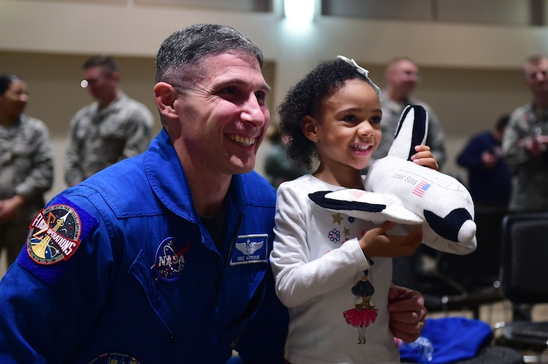 Col. Michael S. Hopkins, astronaut, Air Force National Aeronautics Space Agency, takes a photo with a child the Leadership Development Center, Buckley Air Force Base, Colo., Jan. 8, 2018. The child was upset she was unable to ask Hopkins a question during his presentation so he took time after to take a photo and speak with the little girl about being an astronaut. (U.S. Air Force photo by Senior Airman Luke W. Nowakowski)