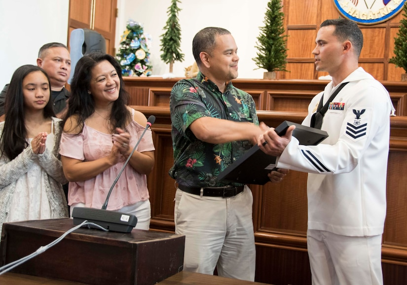 Navy Petty Officer 1st Class Anthony Mugavero, a master at arms assigned to U.S. Naval Base Guam Harbor Patrol, receives a legislative resolution from Guam Sen. Dennis Rodriguez Jr. at the Guam Congress Building in Hagatna, Guam, Dec. 29, 2017. While visiting a mall in nearby Dededo, Mugavero pursued a thief to retrieve a stolen purse. Navy photo by JoAnna Delfin