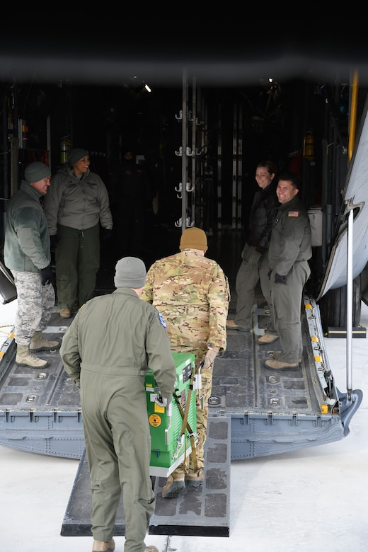 Despite the frigid January temperatures, a group of 932nd Aeromedical Evacuation Squadron (AES) and 932nd Aeromedical Staging Squadron (ASTS) members offload equipment from an equipment truck to to move up the ramp of the C-130 simulator on Jan. 7, 2018, at Scott Air Force Base, Ill.  The 932nd Airlift Wing worked improving and refining skills at the unit during the cold Unit Training Assembly.  The Airmen worked together on first aid skills and C-130 load checks. Simulated patients were moved safely on to a waiting bus, and then out to the aeromedical crew at the C-130 simulator. The compact, highly-packed training was designed to lead people and execute any future medical missions.  (U.S. Air Force photo by Lt. Col. Stan Paregien)