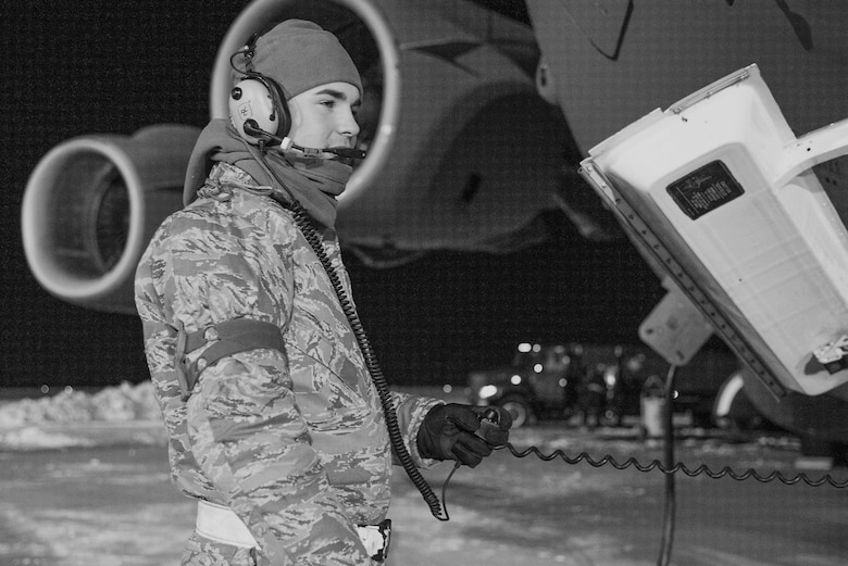 Senior Airman Garrett Battle, 736th Aircraft Maintenance Squadron communication and navigation journeyman, stands near the nose of a C-17A Globemaster III as the aircraft is being refueled, Jan. 5, 2018, at Dover Air Force Base, Del. Battle and other 736th AMXS maintainers prepared the aircraft for a mission in temperatures in the low teens and blowing snow from a steady 15 mile per hour wind. (U.S. Air Force photo by Roland Balik)