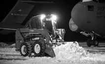 A maintainer from the 736th Aircraft Maintenance Squadron uses a Bobcat to clear snow around a C-17A Globemaster III, Jan. 5, 2018, at Dover Air Force Base, Del. The 436th Operations Support Squadron weather flight recorded eight inches of snow fell on the base from Winter Storm Grayson. (U.S. Air Force photo by Roland Balik)