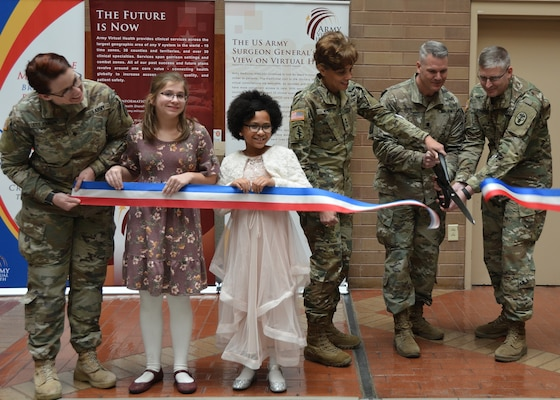 (From left) Lt. Gen. Nadja West, Armyhe Surgeon General and commanding general , U.S. Army Medical Command; Brig. Gen. Jeffrey Johnson, Brooke Army Medical Center commanding general, Lt. Col. Sean Hipp, director of the Army Virtual Medical Center, and children from Fort Sam Houston Elementary School cut the ribbon during the Army Virtual Health Kickoff ceremony Jan. 4.