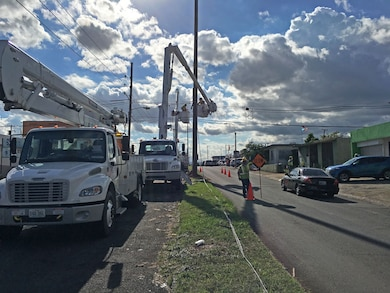 A flagman signals traffic to slow as they pass a crew of linemen from Fluor subcontractor MasTec working on a distribution line in San Juan, Puerto Rico, Dec. 12, 2017, as part of Task Force Power Restoration's mission to repair the island's damaged electrical grid.
