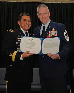 The Adjutant General, New Hampshire National Guard Brig. Gen. David J. Mikolaities, presents the Legion of Merit certificate to Chief Master Sgt. Matthew J. Collier during a ceremony at Pease Air National Guard Base, N.H., Jan. 6, 2017.  Collier retired after 36 years of combined service in the U.S. Air Force and ANG. (N.H. Air National Guard photo by Staff Sgt. Curtis J. Lenz)