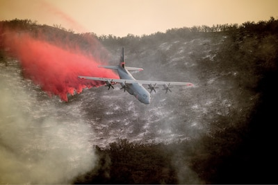 A U.S. Air National Guard C-130J Hercules aircraft equipped with the MAFFS 2 (Modular Airborne Fire Fighting System) drops a line of fire retardant on the Thomas Fire in the hills above the city of Santa Barbara, California, Dec. 13, 2017. The 146th Airlift Wing has been supporting CAL FIRE's efforts to battle the Thomas Fire raging in Southern California. (U.S. Air National Guard photo by Staff Sgt. Nieko Carzis)