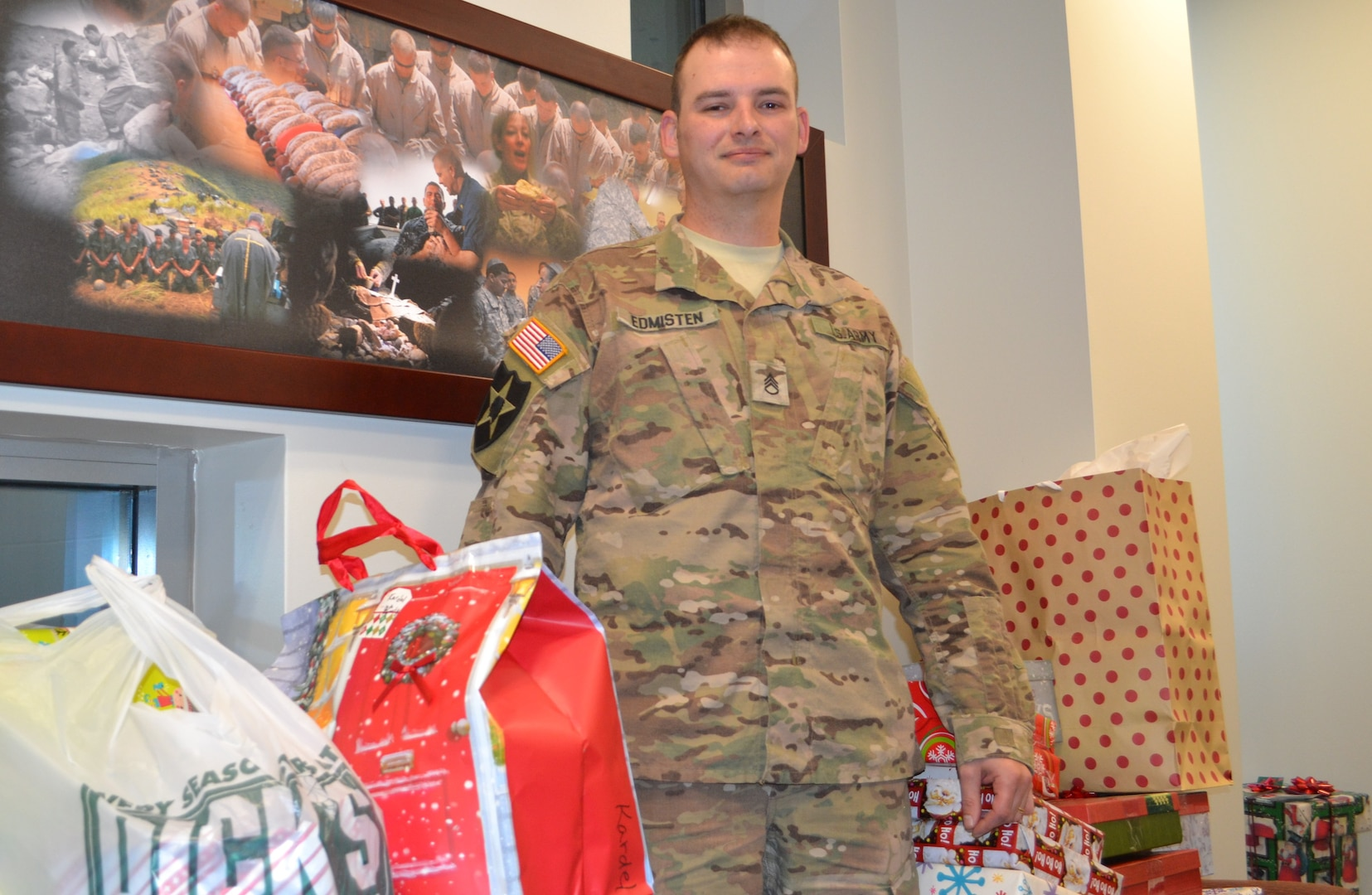 Staff sergeant in ACUs standing with gifts in office, facing viewer