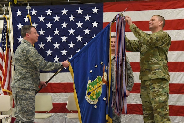 Maj. Gen. Al Dohrmann, the North Dakota adjutant general, right, attaches a streamer, representing the Air Force Outstanding Unit Award, onto the 119th Wing guidon, as Col. Britt Hatley, the 119th Wing commander, lowers the unit flag during a recognition ceremony as Chief Master Sgt. Duane Kangas, the 119th Wing command chief master sergeant, center, looks on at the North Dakota Air National Guard Base, Fargo, North Dakota, Jan. 6, 2018.