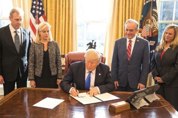President Donald J. Trump signs a document at his desk as officials stand around him.