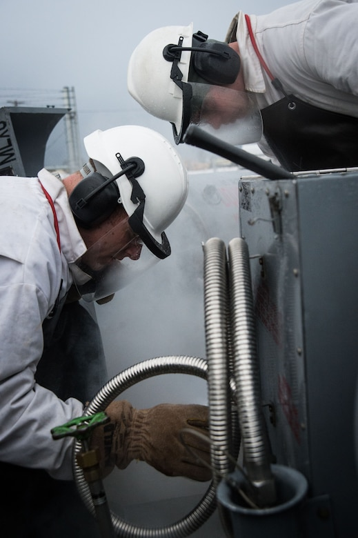 U.S. Air Force Tech. Sgt. Eric Fortenberry (left) and U.S. Air Force Airman 1st Class Jerry Timmons, 673d Logistics Readiness Squadron fuels facilities technicians, take a sample of liquid oxygen at Joint Base Elmendorf-Richardson, Alaska, Dec. 4, 2017. Oxygen is pressurized and cooled into a liquid state in order to transport it more efficiently from cryogenic tanks to JBER's aircraft to provide fresh air to pilots in flight.