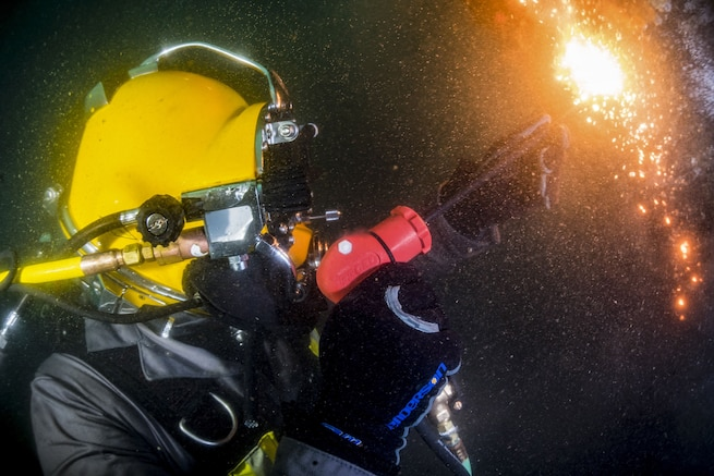Fire and sparks shoot from a torch held by a sailor in a yellow diving helmet.