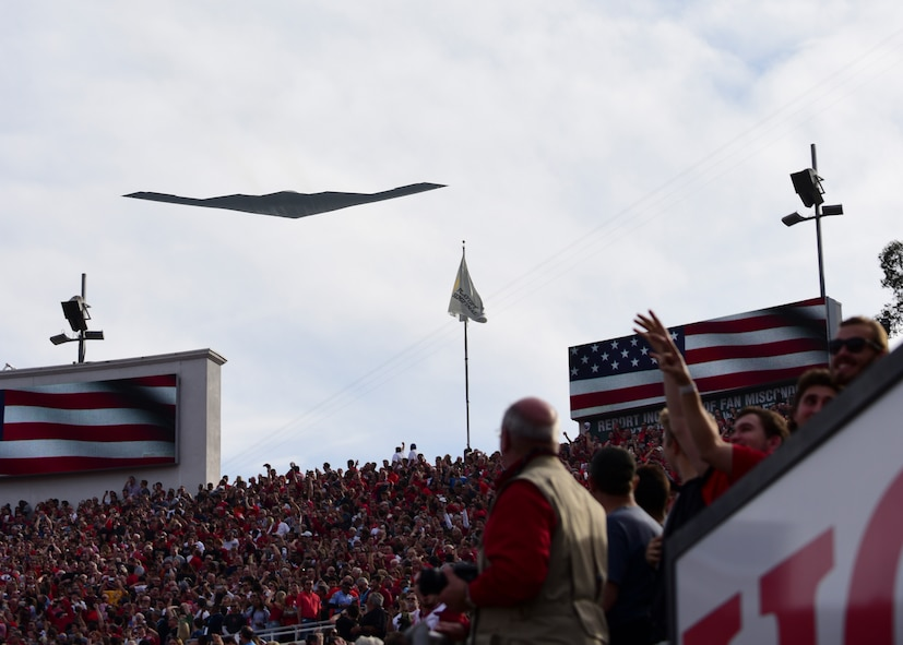 """A B-2 Spirit from Whiteman Air Force Base, Mo., opens the 104th Rose Bowl with a flyover in Pasadena, Calif., Jan. 1, 2018. The B-2 also performed a flyover for the 129th Rose Parade earlier in the day with two F-35 Lightning IIs from Edwards AFB, Calif., to honor U.S. Air Force Maj. Benjamin """"Chex"""" Meier, a pilot assigned to the 31st Test and Evaluation Squadron, and other donors who have given the gift of life to others. (U.S. Air Force photo by Staff Sgt. Danielle Quilla)"""
