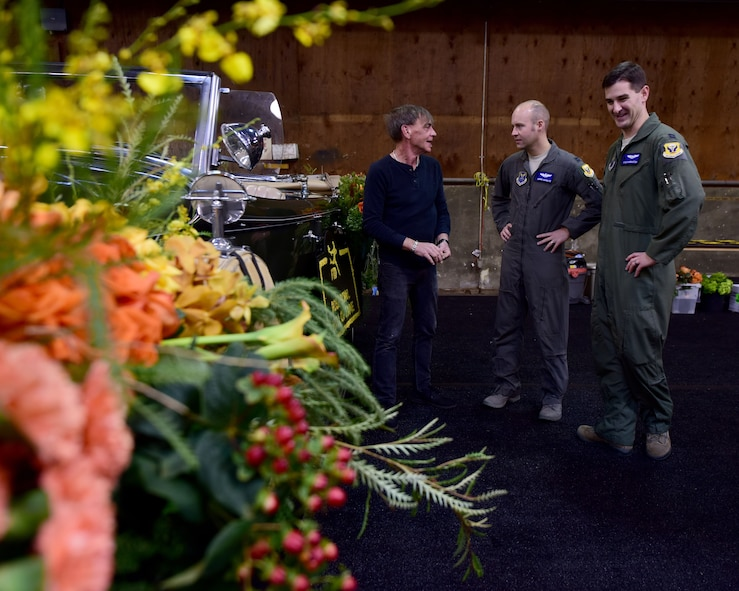 U.S. Air Force Capt. Joseph Manglitz, center, and Capt. Kyle Harrington, talk to Keith White, the florist of the Hall of Fame car for the 2018 Rose Parade, during a tour of the Decorating Places in Pasadena, Calif., Dec. 30, 2017. The car is one of only four cars that appear in the Rose Parade, and this year 2017 Rose Bowl Hall of Fame Inductees Mach Brown, Cade McNown, Charles Woodson and Dr. Charles West were honored with a ride down Colorado Boulevard in the car. (U.S. Air Force photo by Staff Sgt. Danielle Quilla)