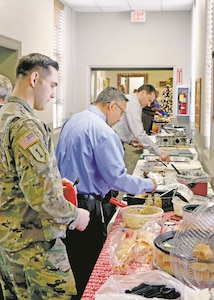Fort Riley garrison employees load up plates for the annual Employee Holiday Potluck Dec. 14. Employees brought growling bellies and left with smiles as the annual potluck ended with a few pounds added.