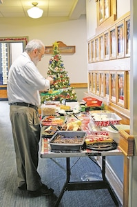 Kirk Hutchinson, public affairs specialist Fort Riley garrison, adds a few sweets to his plate at the Fort Riley garrison Employee Holiday Potluck Dec. 14. Each garrison organization was assigned to bring one meat, sides, fruit, desserts, drinks, plates or cutlery.