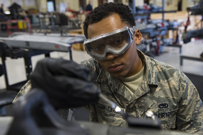 Airman 1st Class DeAndre Hilton-Cardoza, 23d Maintenance Squadron armament apprentice, paints metal elements with anti-corrosion spray, Jan. 10, 2018, at Moody Air Force Base, Ga. Moody's armament flight is responsible for maintaining all of the aircraft weapons systems components when they're removed from the aircraft. This includes gun systems, alternate mission equipment and bomb racks. (U.S. Air Force photo by Senior Airman Janiqua P. Robinson)
