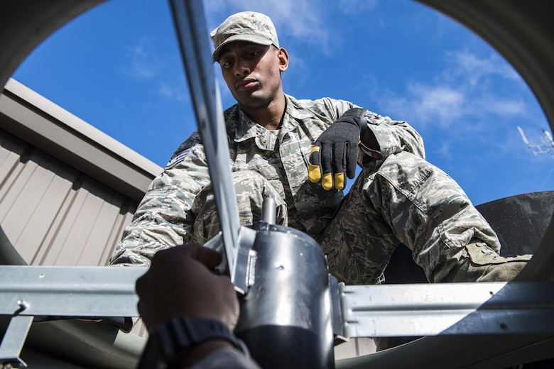 Staff Sgt. Zachary Pigg, 23d Civil Engineer Squadron Heating, Ventilation and Air Conditioning (HVAC) journeyman, helps secure a fan motor, Jan. 10, 2018, at Moody Air Force Base, Ga. The equipment that keeps Moody comfortable indoors is designed for a climate that is typically warm year round, but when temperatures fall below 40 degrees, the equipment starts to malfunction. With temperatures recently dipping into the low teens and snow falling this winter for the first time since 2010, Airmen who work in Moody's HVAC flight credit the weather for the busy winter they're having. (U.S. Air Force photo by Senior Airman Janiqua P. Robinson)