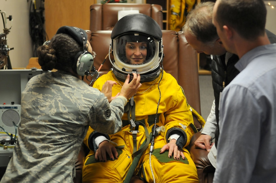 Katherine Segovia, Executive Education Head of Learning Experience Design at Stanford University Design School, is assisted while putting on an Air Force U-2 Dragon Lady flight suit as part of her visit for a design thinking seminar on the Inaugural Design Day