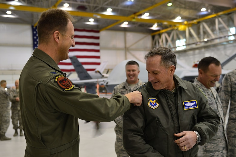 Col. Cheater, 432nd Wing/432nd Air Expeditionary Wing commander, puts the 432nd WG patch on Air Force Chief of Staff Gen. David L. Goldfein Jan. 9, 2017, at Creech Air Force Base, Nev. Goldfein toured operational squadrons around the base to meet with 432nd Wing/432nd Air Expeditionary Wing and 799th Air Base Group Airmen. (U.S. Air Force photo/Airman 1st Class Haley Stevens)