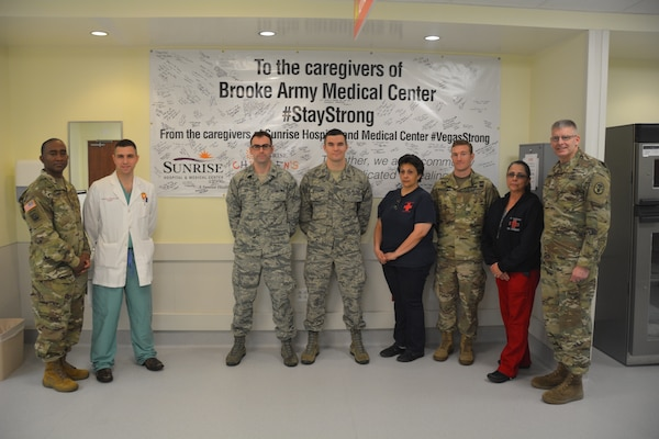 Brooke Army Medical Center Commanding General Brig. Gen. Jeffrey Johnson (far right), Command Sgt. Maj. Diamond Hough (far left) and Emergency Department personnel pose in front of a #StayStrong banner in the ED. Sunrise Hospital and Medical Center sent the banner as a show of support to BAMC after the Sutherland Springs shooting Nov. 5, 2017. Sunrise Hospital treated more than 200 injured in the Las Vegas shooting last October. BAMC, which treated eight victims from Sutherland Springs, plans to rotate the banner throughout the hospital in the coming months to share the banner, which is filled with well-wishes and messages of hope and support.