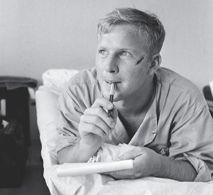 Army medic Thomas Cole writes a letter home while recovering from a head wound at the Third Field Hospital in Saigon on Feb. 19, 1966. Cole made national headlines when a photo of him appeared on the cover of Life magazine. That photo is on the cover of this month's VFW. (Photo by Henri Huet/AP)