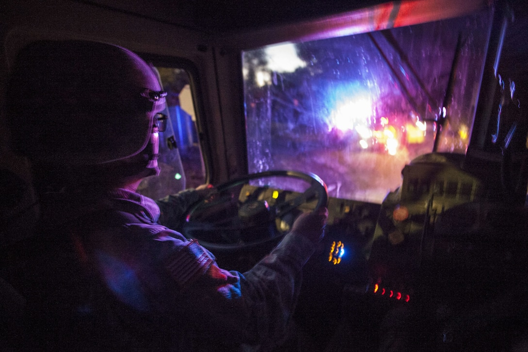 A soldier wearing a helmet drives a tactical vehicle in the dark, as colored lights illuminate the windshield.