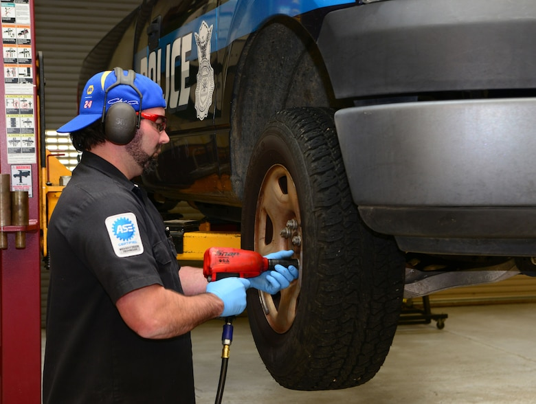 Bart Hicks, 9th Support Division vehicle maintenance work leader removes a tire from a police vehicle