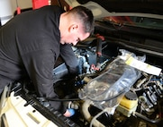 Michael Brink, 9th Support Division automotive mechanic, changes an air conditioning bracket in a chase car