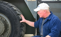 Darryl Crady, 9th Support Division heavy mobile equipment mechanic, inspects a damaged tire