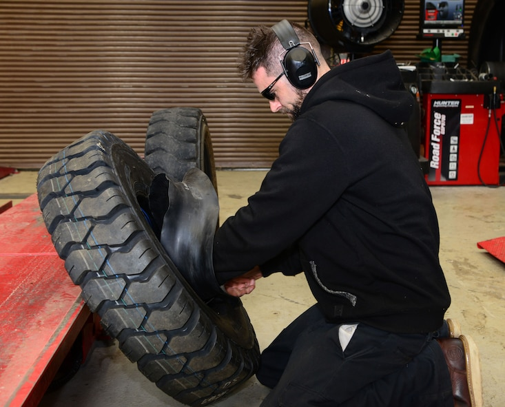 Eric Ford, 9th Support Division mobile maintenance mechanic, replaces a tube in a tire