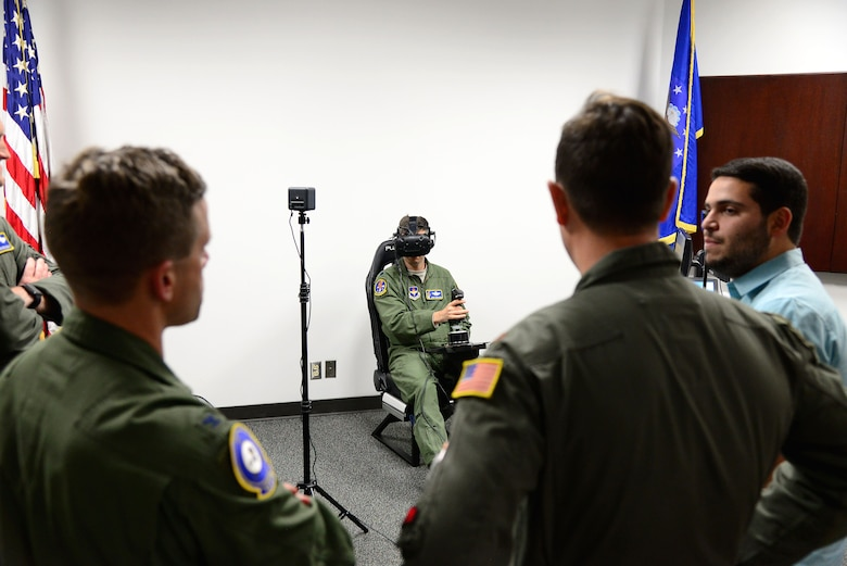 Col. William Denham, 14th Flying Training Wing Vice Commander, and the Adaptive Flight Training Study research team look onto Lt. Col. Marc Deshaies, 14th Student Squadron Commander as he flies a virtual aircraft Jan. 9, 2018, on Columbus Air Force Base, Mississippi. The study was held primarily to find out if the VR environment would help adults learn at or above the rates they are currently learning, and how the brain works and reacts in conjunction with other parts of the body during the learning process.