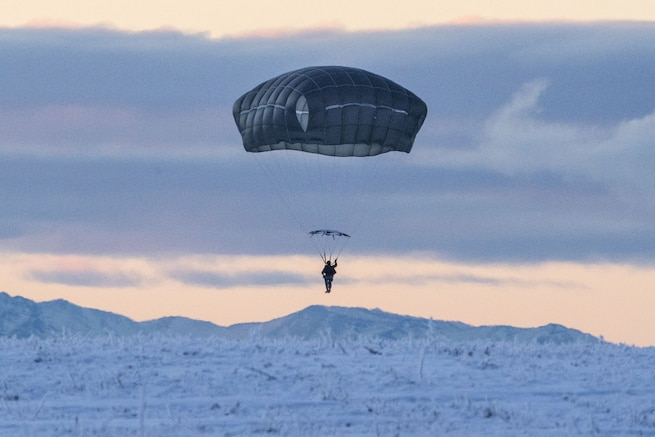A soldier parachutes above a backdrop of snowy mountains and pale blue and pink sky.