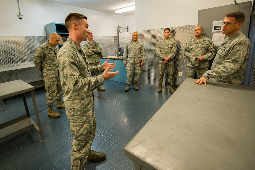 """U.S. Air Force 2nd Lt. Robert """"Bo"""" Huebel, left, 437th Aircraft Maintenance Squadron sortie support flight commander, briefs Brig. Gen. Steven J. Bleymaier, director of logistics, engineering and force protection, Headquarters Air Mobility Command, Scott Air Force Base, Ill at Joint Base Charleston. Jan. 10, 2018."""