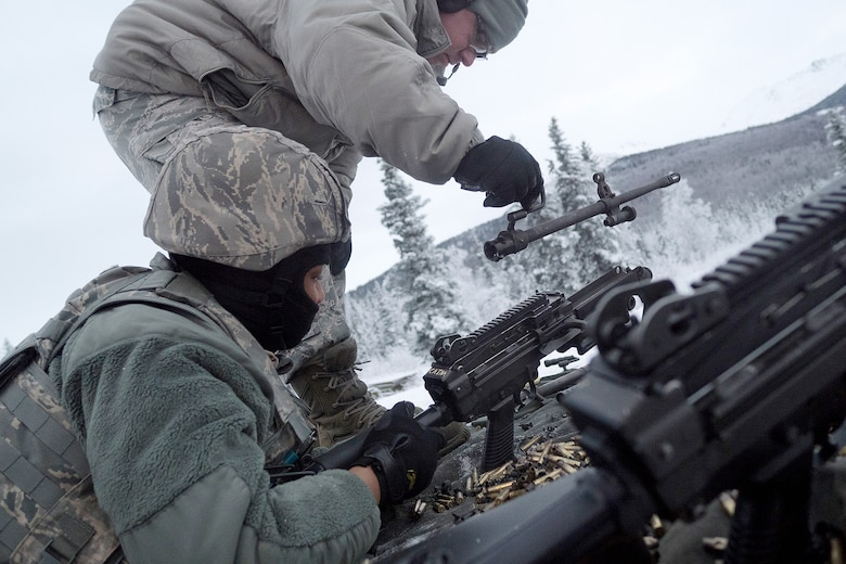 Senior Airman Cody Morgan, a native of New Salisbury, Ind., removes the barrel of an M249 Squad Automatic Weapon for Airman 1st Class Kaylon Thomas, a native of Conway, Ark., as Airmen assigned to the 673d Security Forces Squadron conduct machine gun qualification range on Joint Base Elmendorf-Richardson, Alaska, Jan. 10, 2018. Security Forces Airmen perform extensive training in law enforcement as well as combat tactics to protect U.S. Military bases and assets both stateside and overseas.