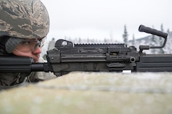 An Airman assigned to the 673d Security Forces Squadron lines up a traget with an M249 Squad Automatic Weapon during machine gun qualification range on Joint Base Elmendorf-Richardson, Alaska, Jan. 10, 2018. Security Forces Airmen perform extensive training in law enforcement as well as combat tactics to protect U.S. Military bases and assets both stateside and overseas.