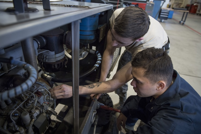 Airman 1st Class Cody Noel, 374th Maintenance Squadron aerospace ground equipment technician, teaches a fellow AGE Airman about how to properly fix a piece of equipment, Jan. 10, 2018, at Yokota Air Base, Japan.