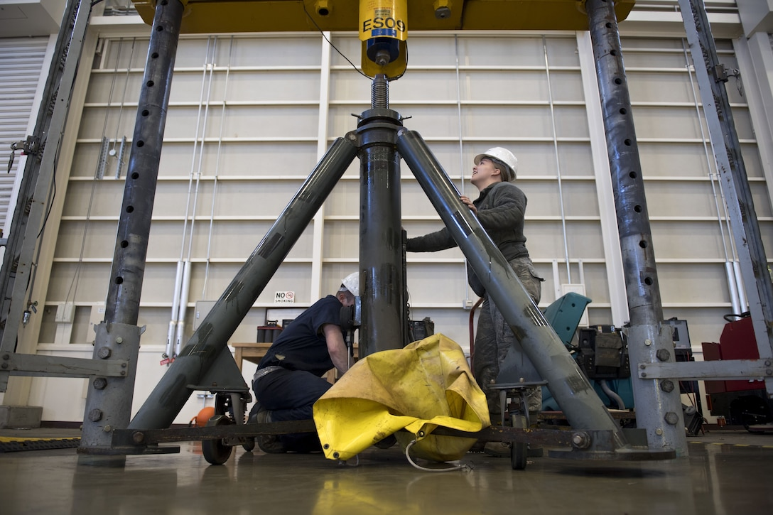 Airman 1st Class Sommer Lax, 374th Maintenance Squadron aerospace ground equipment technician, guides a 60 ton aircraft jack into place in a universal jack tester, Jan. 10, 2018, at Yokota Air Base, Japan.