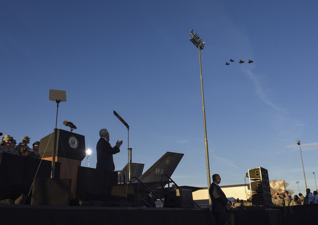 Vice President Mike Pence applauds as two F-35 Lightning II fighter jets, assigned to the 6th Weapons Squadron, and two F-22 Raptor fighter jets, assigned to the 433rd WPS, thunder overhead during his visit at Nellis Air Force Base, Nevada, Jan. 11, 2018. Following the fifth-generation aircraft flyover, Pence turned toward his audience to express his gratitude for a vast history of air superiority. (U.S. Air Force photo by Airman 1st Class Andrew Sarver)