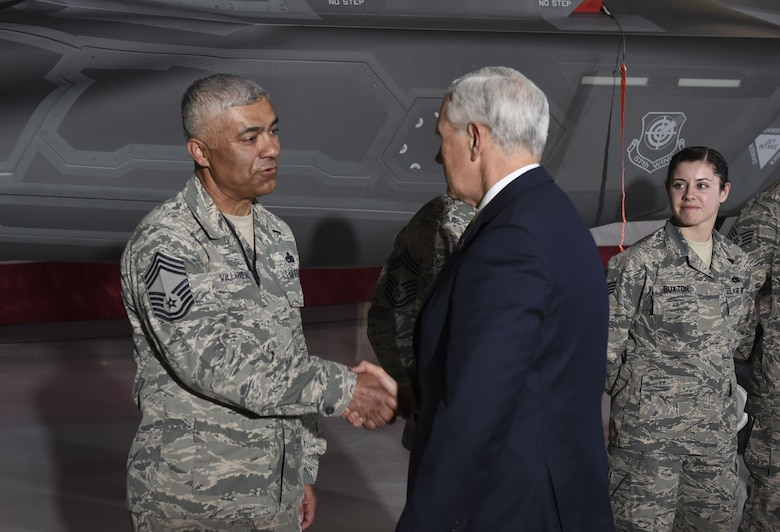 Vice President Mike Pence shakes hands with Chief Master Sgt. Raul Villarreal, 57th Maintenance Group chief enlisted manager, after meeting Staff Sgt. Samantha Buxton, 57th Aircraft Maintenance Squadron F-35 crew chief, during his tour of the F-35 Lightning II fighter jet in the Thunderbirds Hangar at Nellis Air Force Base, Nevada, Jan. 11, 2018. Pence praised Nellis Airmen for its long-standing dedication to air superiority. (U.S. Air Force photo by Airman 1st Class Andrew Sarver)