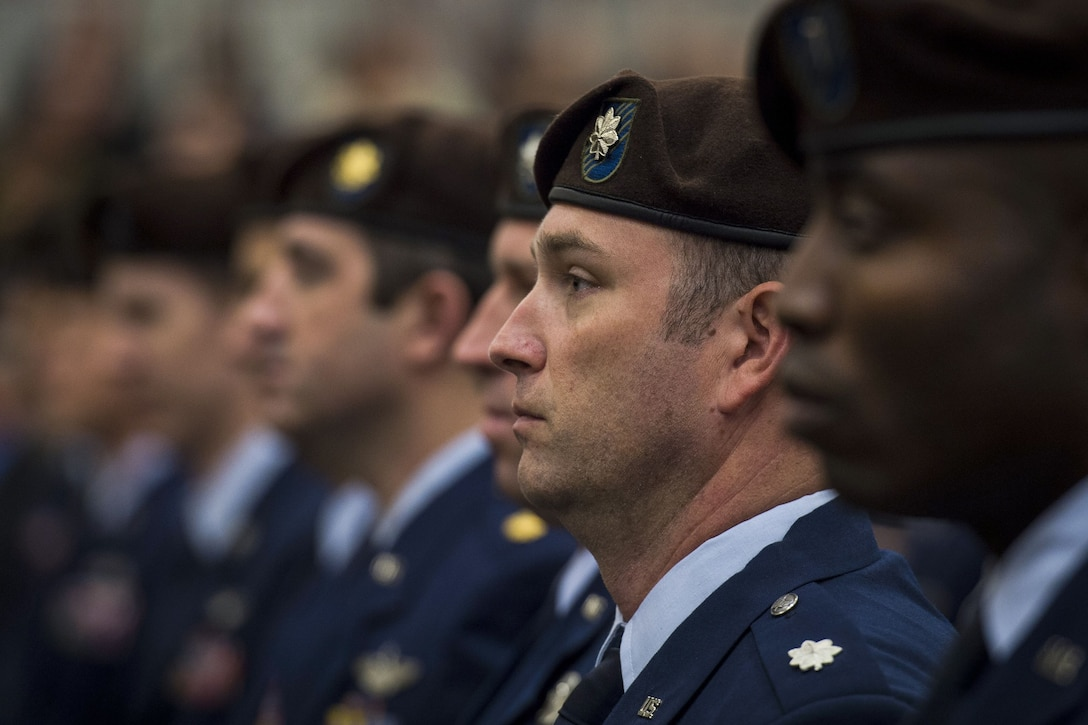Airmen, shown in profile from the shoulders up, stand in a row wearing brown berets.