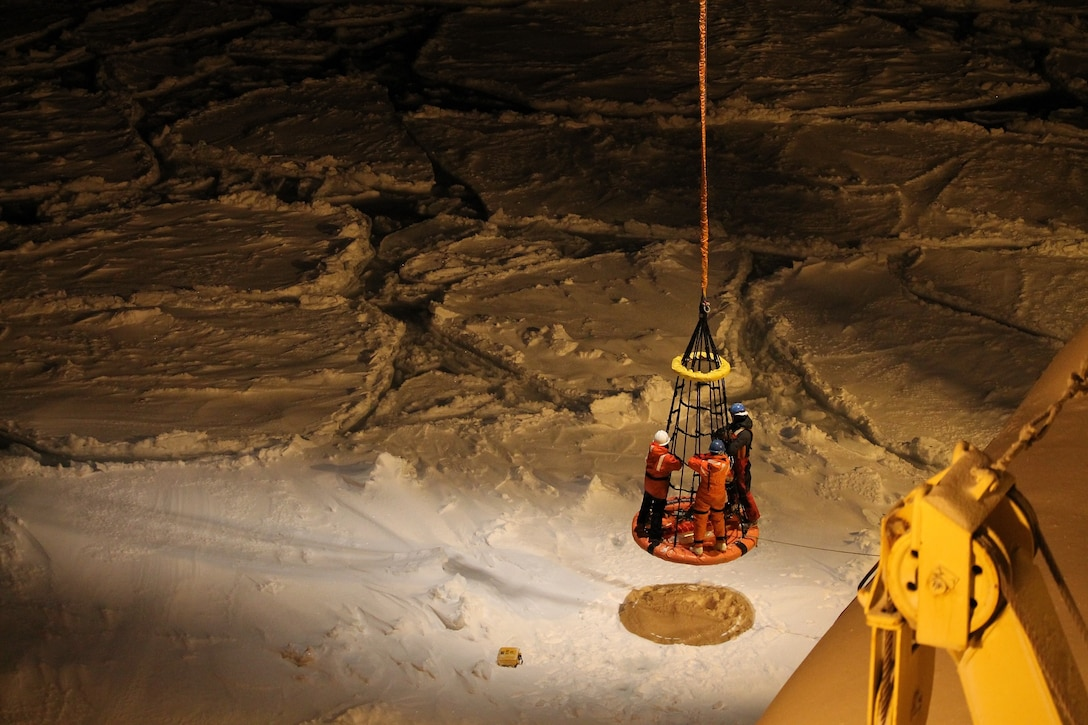 Researchers are lifted from the sea ice to the icebreaker Nathaniel B. Palmer after placing a buoy that measures waves traveling through ice in the marginal ice zone.