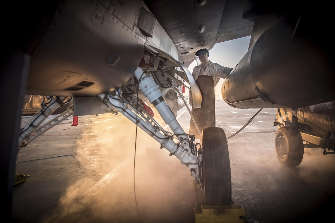 Senior Airman Austin Boyd, of the 138th Fighter Wing, attaches a hose containing liquid oxygen to an F-16 Fighting Falcon, Feb. 1, 2017. (U.S. Air National Guard photo/Tech. Sgt. Drew A. Egnoske)