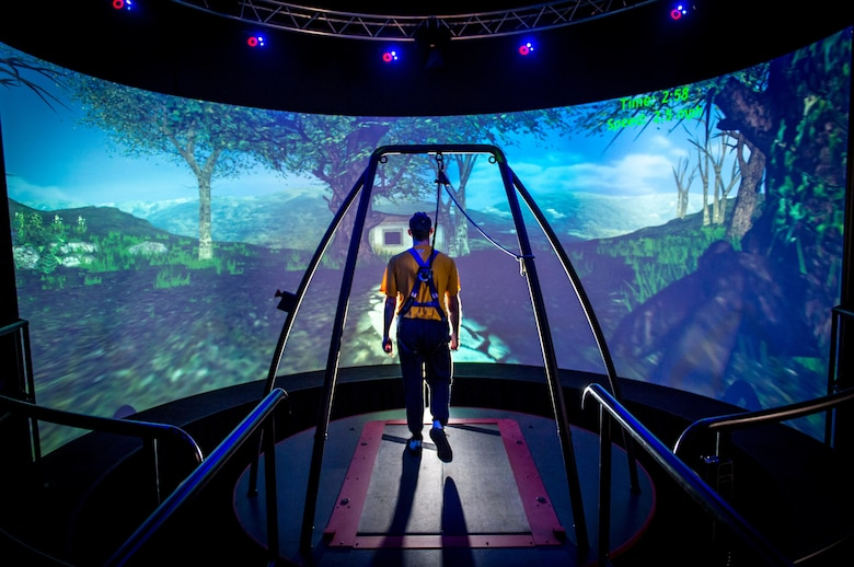 A Traumatic Brain Injury (TBI) patient walks through a virtual reality scenario at the Computer Assisted Rehabilitation Environment (CAREN) Laboratory at National Intrepid Center of Excellence (NICoE) at Walter Reed National Military Medical Center in Bethesda, Md., March 20, 2017. The patient is attached to a safety harness and walks on a treadmill on a platform that moves and rotates in conjunction with movements of the projected environment. Motion capture cameras track the patient's movements via reflective markers that are applied to the patient and supply data on physical deficits to physical therapists. (U.S. Air Force photo by J.M. Eddins Jr.)